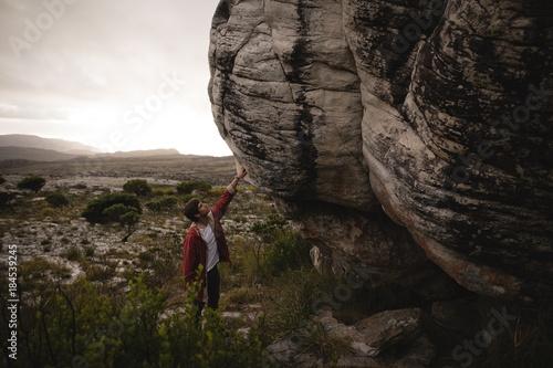 Man standing under cliff