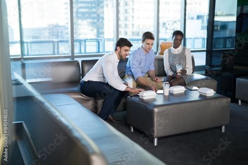 Fototapeta Male and female executives having snacks obraz na płótnie