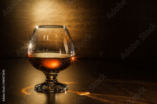 Fotobehang Alcohol Cognac drinks glass on dark background