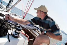 Man Hoisting Sail On Yacht