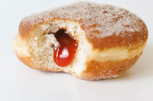 German Fried Donut, So Called Krapfen, Berliner Or Pfannkuchen, Filled With Rose Hip Jam And Dusted With Cinnamon Sugar, Traditionally Eaten At Carnival And At New Year's Eve On White Background