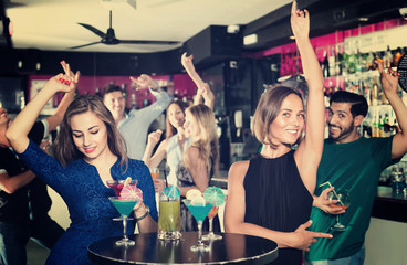 Women are drinking cocktails and having fun in nightclub.