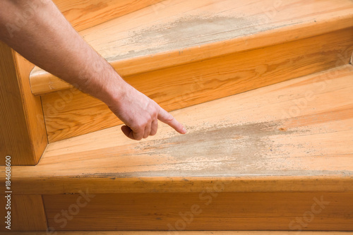Man's hand pointing to the old scratched wooden stairs' step in the house. Problems and solutions concept.