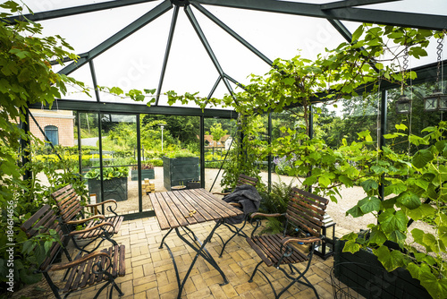 Fotografering Terrace in a glass house with wooden garden furniture