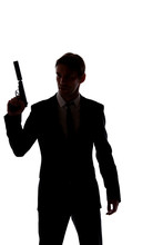 Silhouette Of Man In Business Suit With Gun At Hand Isolated On White Background