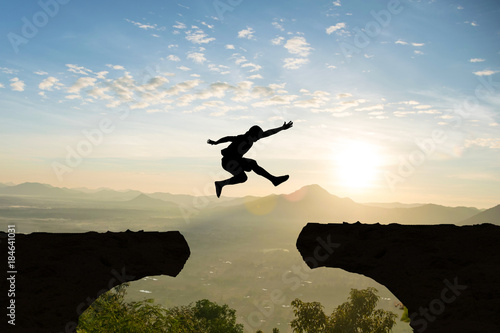 Man jump Mountain cliff sun light over silhouette Wallpaper Mural