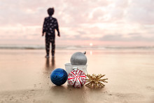 Child Looking At Sunset At Carlsbad State Beach And Christmas Decorations On The Background Of Sea, California