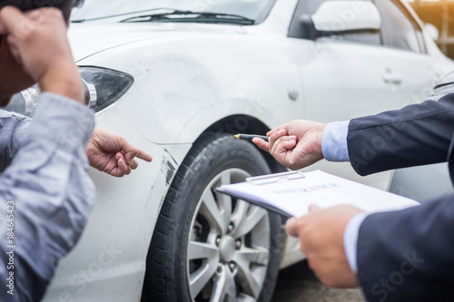 Insurance agent writing on clipboard while examining car after accident claim being assessed and processed.
