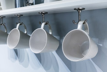 Row Of White Ceramic Cups Hang...