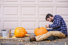 Man Sitting Outdoors Carving A...