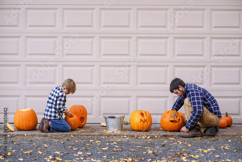 Attirant Father And Son Sitting By A Garage Door Carving Halloween Pumpkins