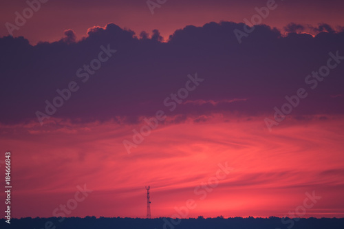 Tuinposter Crimson tower on the horizon against the background of the setting sun in the color of the year 2018 ultra violet