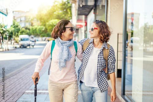 Stylish and beautiful mature mother and adult daughter are walking along the street Fototapeta