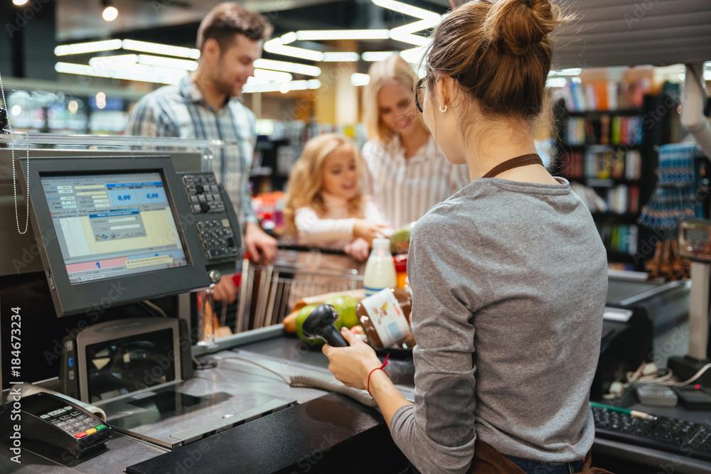 Fototapeta Beautiful family standing at the cash counter