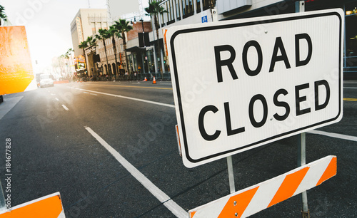 Road closed sign and traffic cone in the street. Traffic control sign road closed in the city. Road closed sign on Hollywood Boulevard.