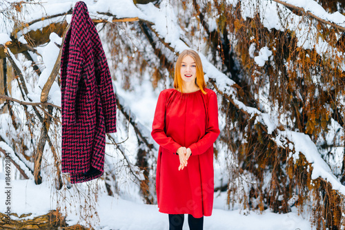 Young beautiful red haired foxy girl freezing in snowy forest  Odd