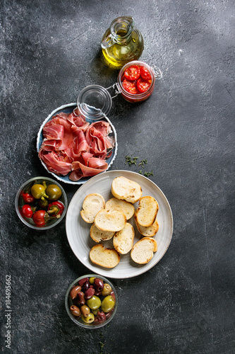 Ingredients for making tapas or bruschetta. Crusty bread, ham prosciutto, sun dried tomatoes, olive oil, olives, pepper, greens on plates over dark texture background. Top view with space