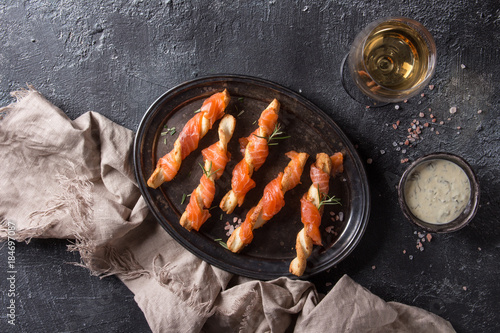 Foto op Plexiglas Voorgerecht Appetizer with smoked salmon on crispy breadsticks served on vintage metal tray with cheese dill sauce, sea salt, glass of white wine, textile napkin over black texture background. Top view with space