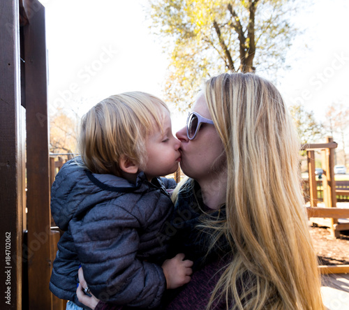 A Caucasian Toddler Gets A Kiss From His Mom In A Public Park