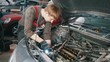 Mechanic with lamp repairs automotive engine, car repair, working in the workshop