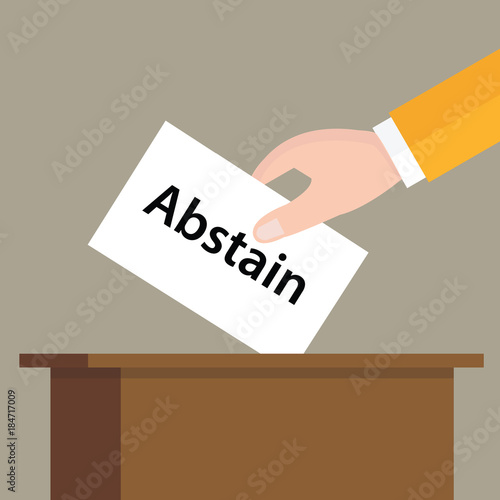 Photo abstain choice vote hand putting a ballot paper in a slot of box