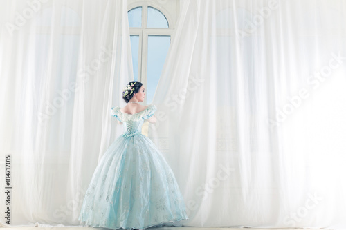 Photographie  Elegant woman at a high window in historic dress, straightens the curtains, and