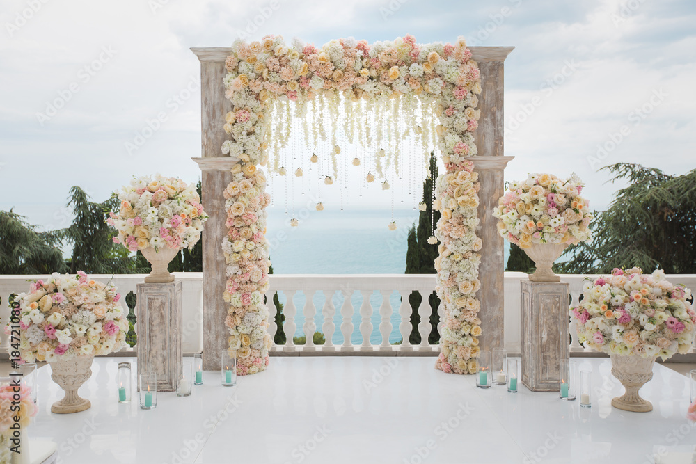 Fototapety, obrazy: Elegant wedding arch with fresh flowers, vases on background of ocean and blue sky.