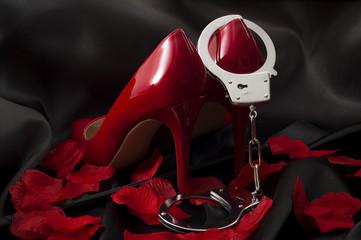 Koncepcja BDSM, prostytucji i dewiacyjnych zachowań seksualnych z plonem jeździeckim, czerwonymi szpilkami na wysokich obcasach, płatkami róż i kajdankami z plonem biegnącym pod obcasami butów na czarnym jedwabiu