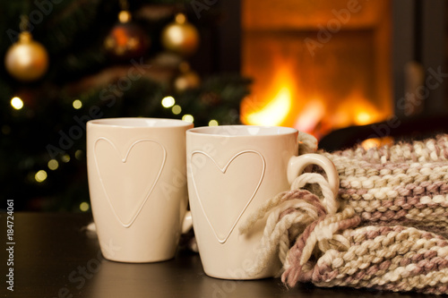 In de dag Chocolade two tea mugs, knitted scarf and christmas tree and fireplace in the background - hygge concept