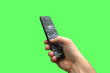 canvas print picture - Remote control in hand on isolated green screen background