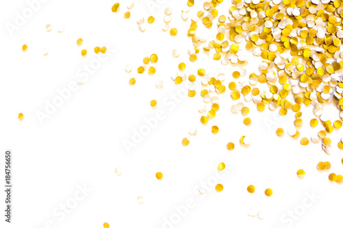 Golden shiny confetti on a white background.