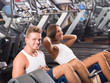 man and woman doing abs exercise in gym .
