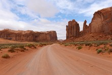 Red Desert Valley Road - A Unpaved Dirt Road Winding Through Red Sandstone Desert Valley In The Famous Monument Valley, Utah & Arizona, USA.
