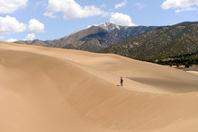Hiking On Sand Dunes - A Tourist Is Hiking On A Sand Ridge On A Spring Day At Great Sand Dunes National Park, Colorado, USA. The Park Sits At West Base Of Sangre De Cristo Range In San Luis Valley.