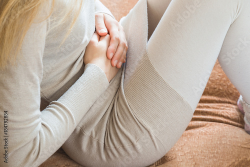 Photo  Woman's hand touching her belly because she suffering from abdominal pain at home in the bed