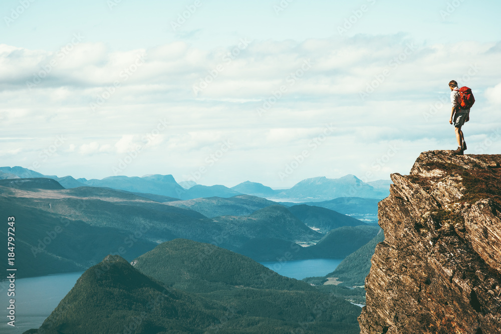 Fototapety, obrazy: Man explorer standing on cliff alone mountain summit over fjord Norway landscape Travel Lifestyle success motivation concept adventure active vacations outdoor