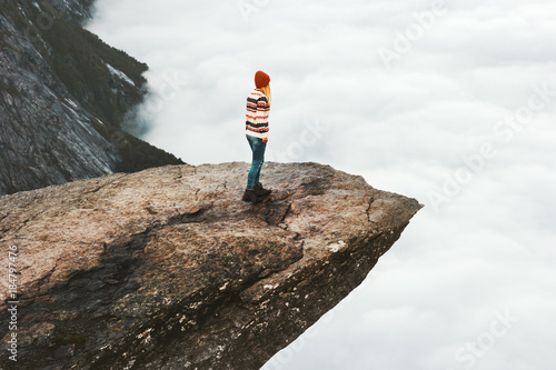 Woman explorer walking on Trolltunga rocky cliff in Norway mountains Travel Lifestyle adventure concept extreme vacations outdoor above clouds