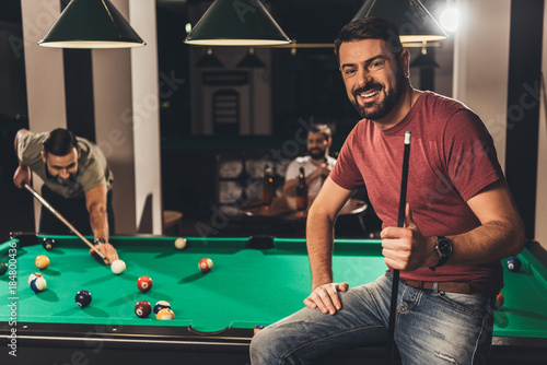 Canvas young handsome caucasian man beside billiard table in bar with friends