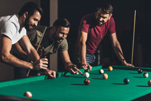 Group Of Young Handsome Men Playing In Pool At Bar