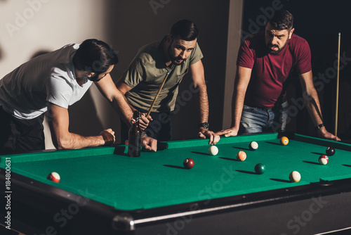 Fotografia three handsome caucasian men playing in billiard at bar