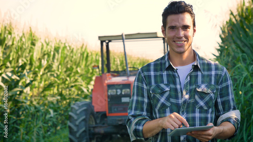 Foto Portrait of a beautiful young farmer (student) working in the field with a tractor working in a tablet, happy, in a shirt, corn field