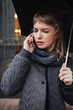 Portrait of upset lady standing on street with black umbrella and talking on her cellphone isolated