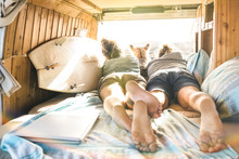 Hipster Couple With Cute Dog Traveling Together On Vintage Van Transport - Life Inspiration Concept With Hippie People On Minivan Adventure Trip Watching Sunset In Relax Moment - Warm Sunshine Filter
