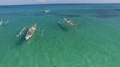 Philippine fishing ships resting in beautiful calm ocean, aerial shot