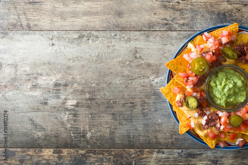 Mexican nachos with beef, guacamole, cheese sauce, peppers, tomato and onion in plate on wooden table. Top view
