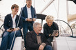 Senior couple using digital tablet while traveling with friends in yacht