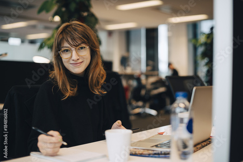 Portrait of confident young businesswoman holding pen while sitting at desk in office