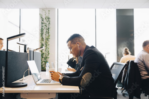 Businessman listening to music through smartphone in office