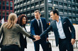Smiling business people stacking hands against office building