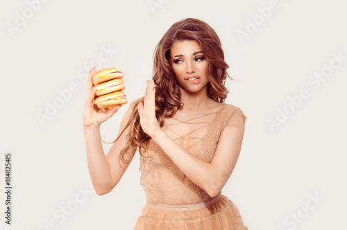 Photo Woman has craving for fast food in her hand, she is hardly abstaining avoiding to eat it, gesturing stop no with other hand isolated white background